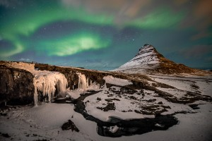 The aurora shines over Kirkjufell.