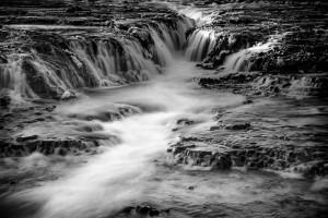 Water cascades down a waterfall near Geysir.